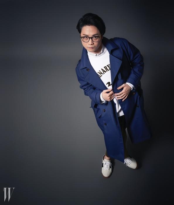줄무늬 패턴의 셔츠와 금색 로고가얹힌 맨투맨, 카키색 팬츠와 남색트렌치코트는 모두 오디너리 피플,파란 프레임의 안경은 에나로이드 바이 옵티컬더블유, 스니커즈는 프레드 페리 제품.