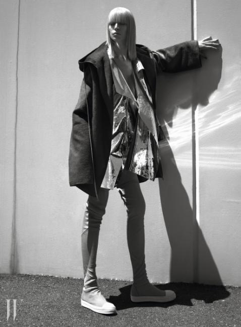 커다란 후드가 특징인 코트와운동화와 결합된 형태의 사이하이 부츠는Rick Owens, 메탈릭한 소재의베스트는 Gareth Pugh 제품.