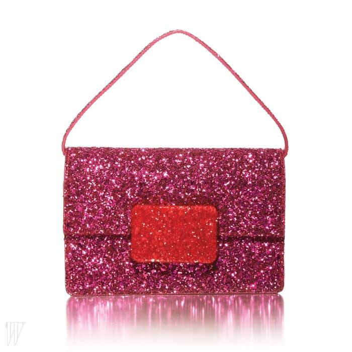 단순한 모양새에 반짝이는 분홍색의 표면이 돋보이는 생로랑의 핸드백.