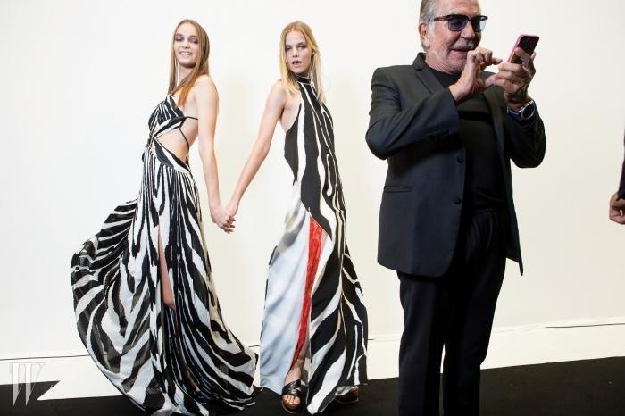 모델들이 두 손을 맞잡은 채유쾌한 포즈를 취하는 순간에도스마트폰 삼매경에 빠진로베르토 카발리.