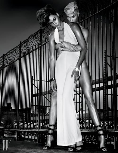 흰색 홀터넥 점프수트는 Balmain,오른쪽 귀에 착용한 귀고리는 Tiffany & Co.,다이아몬드가 세팅된 이어커프는 Phyne by Paige Novick,은 소재 커프는 Tiffany & Co.,금색 버클과 스트랩이 특징인 가죽 샌들은 Anthony Vaccarello X Versus Versace 제품.