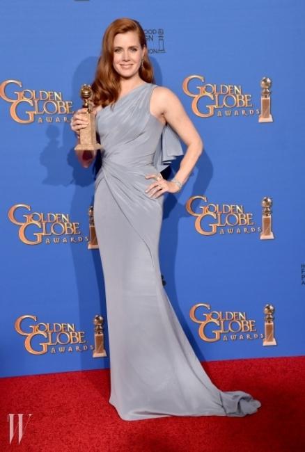 에이미 아담스 - 2년 연속 골든 글로브 여우 주연상을 거머쥔 에이미 아담스. 그녀는 심플하지만 보디라인을 부드럽게 감싸 여성미를 극대화한 베르사체의 드레스를 선택했다. 착용한 주얼리는 모두 티파니 앤 코 제품.