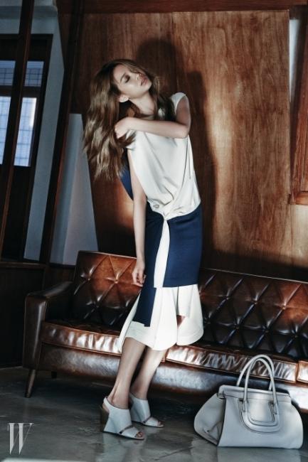 배색이 멋진미디 드레스와 겹쳐 입은 스커트,조형적인 샌들과 바닥에 놓인E라인 에버스톤 토트백은 모두 Chloe 제품.