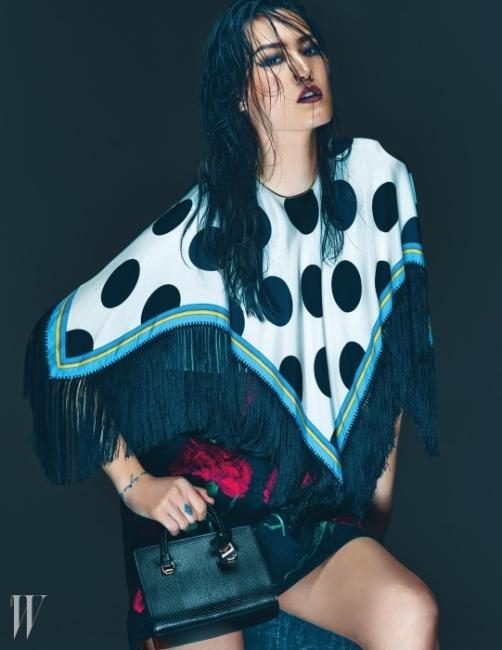 리드미컬한 도트무늬와술 장식이 어우러진 판초가 더해진 톱,카네이션 프린트 스커트, 클래식한 백은모두 Dolce & Gabbana 제품.
