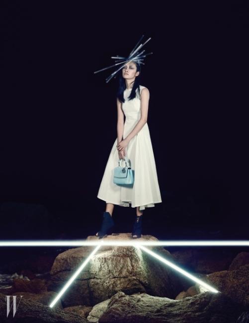 실루엣에 집중한담백한 디자인에서 궁극의미니멀리즘이 느껴지는 드레스,건축적인 커팅의 부티, 청명한 색감의사첼백은 모두 Dior 제품.
