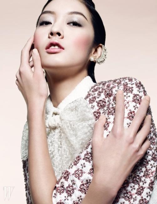 Chanel이번 시즌 칼 라거펠트는 동시대의 여성에 주목했다. 런웨이는 봄을 닮은 생기발랄한 컬러의 룩으로 가득했는데 모델들의 얼굴 역시 싱그럽기 그지없었다. 반짝이는 피부 위에 오간자를 드리운 듯 아른거리는 아이 메이크업과 은은한 핑크빛 립이 포인트!결점 없이 반짝거리는 피부를 만들기 위해 라이트 크리에이터 화이트닝 메이크업 베이스 SPF 40/ PA+++(30호)를 바른 뒤 뻬르펙씨옹 뤼미에르 벨벳 SPF 15를 얇게 펴 발랐다. 투명하게 반짝이는 눈매는 레 꺄트르 옹브르(238호)의 가장 밝은 색과 일뤼지옹 동브르(미스터리오)를 겹쳐 발라 연출한 것. 화사함을 더해주기 위해 입술에는 하모니 레브르 아라베스크의 코럴 핑크 색상의 립글로스를, 양 볼에는 쥬 꽁뜨라스트(크레센도)를 가볍게 터치해줬다. 모두 Chanel 제품.진주 장식의 이어커프와 붉은 크리스털로 장식된 볼레로와 흰 원피스는 모두 Chanel 제품.