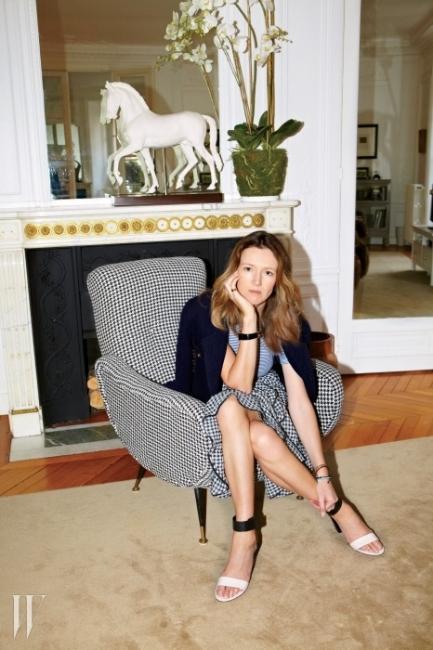 거실의 마르코 자누소 체어에 앉은 웨이트 켈러.