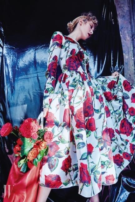 탐스러운 장미가풍성하게 피어난 로맨틱한드레스와 빨간 가죽 소재토트백은 Dolce&Gabbana 제품.