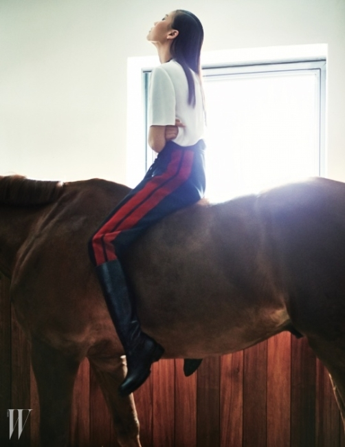미색의 심플한 톱과 허리의로프 장식이 멋진 네이비 팬츠, 터프한롱부츠는 모두 Lanvin 제품