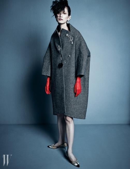 우아한코쿤 실루엣의 코트,반짝이는 브로치들과진주 이어커프,크리스털 장식의스틸레토 슈즈는모두 Balenciaga 제품.
