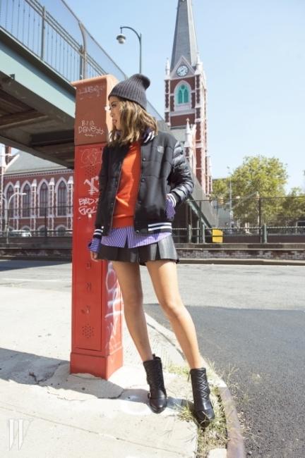 경쾌한 베이스볼 점퍼와줄무늬 보라색 셔츠, 주황색 니트 톱,검정 플레어 스커트, 회색 비니,검정 원석 귀고리, 버클 장식 부츠는 모두Polo Ralph Lauren 제품.