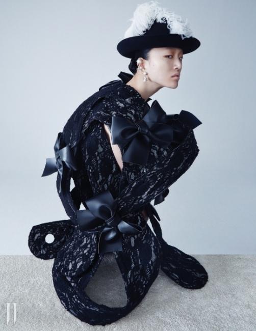 구조적인 형태의가죽 리본 장식 레이스 드레스는Comme des Garcons,깃털 장식 페도라는 Chanel,진주 장식 이어링은모두 Balenciaga 제품.