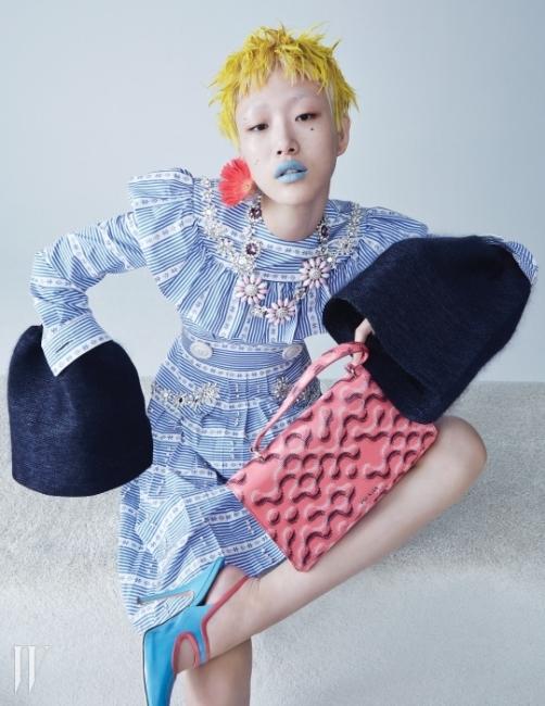사랑스러운 줄무늬 드레스와 플라워 목걸이는 Miu Miu, 셔츠 안에 입은 풍성한 소매 장식 톱은 Celine,그래픽 패턴이 돋보이는핑크색 토트백은Miu Miu 제품.
