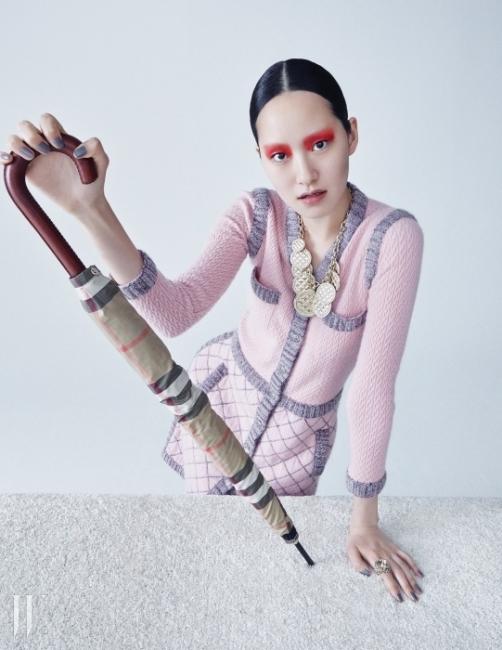 핑크색 클래식 니트 드레스와 퀴팅 디테일의 코인 목걸이는 모두 Chanel, 체크 무늬우산은 Burberry, 빈티지한 호랑이 반지는 Gucci 제품.