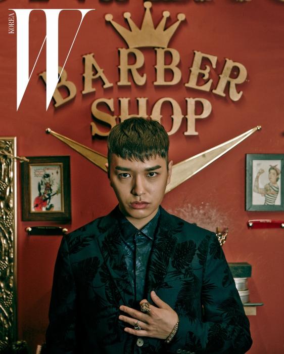 야자수 패턴이 더해진슈트는 Alexander Wang by MUE,화려한 프린트 셔츠는Valentino by MUE,해골과 나사 못에서 힌트를 얻은두 개의 반지와남성적인 팔찌는모두 Endymion 제품.