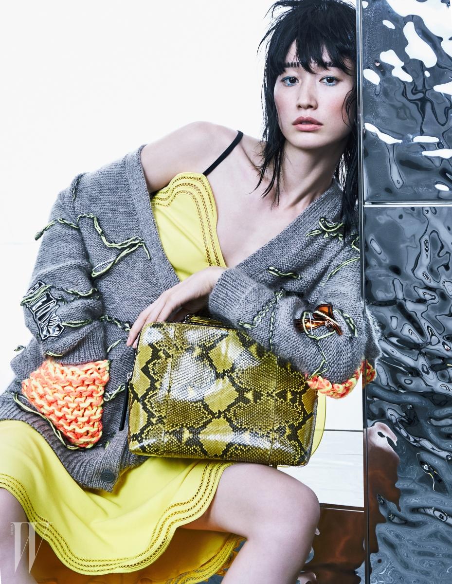 물결 형태의 샛노란 슬리브리스 드레스와 실이 풀린 듯한 세부 장식이 멋스러운 니트 카디건, 뱀피무늬 가방은 모두 크리스토퍼 케인.
