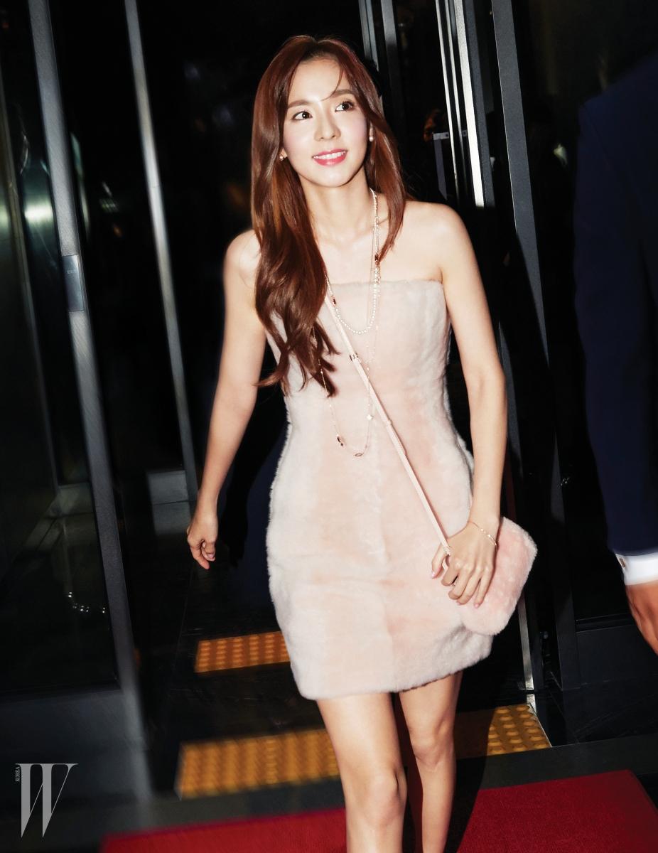 연한 핑크색의 양털 튜브톱 드레스와 크로스로 연출한 미니 피카부 백은 모두 Fendi 제품.