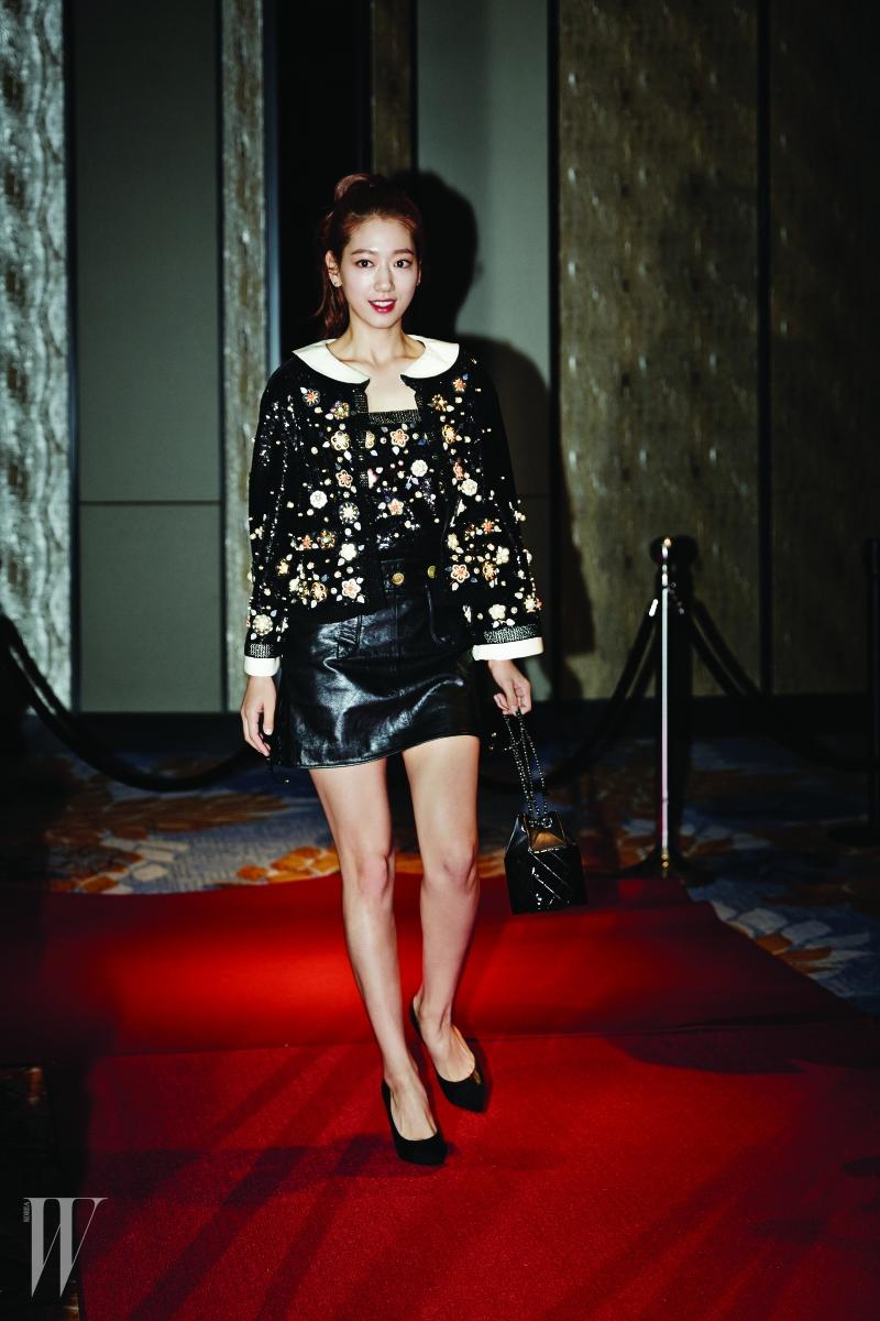 꽃 모티프 주얼 장식 재킷과 톱, 가죽 스커트, 펌프스와 퀼팅 체인 백은 모두 Chanel 제품.