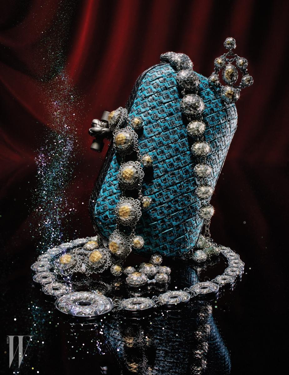 나파 가죽과 물뱀의 일종인 에이어스 소재가 고급스럽게 조합된 청량한 푸른색의 놋 클러치, 입체감 있는 카보숑 컷의 오벌형 스콜피토 아르젠토 펜던트가 연결된 인트레치아토 스콜피토 아르젠토 주얼리 컬렉션의 목걸이와 팔찌, 귀고리는 모두 Bottega Veneta의 크루즈 컬렉션 제품.