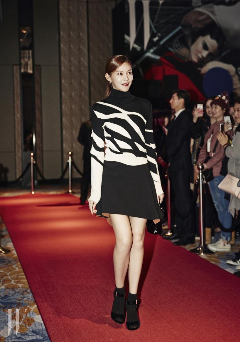 모던한 레이디라이크 룩 니트 톱과 스커트, 페이턴트 가죽 미니 토트백은 모두 Dior 제품.