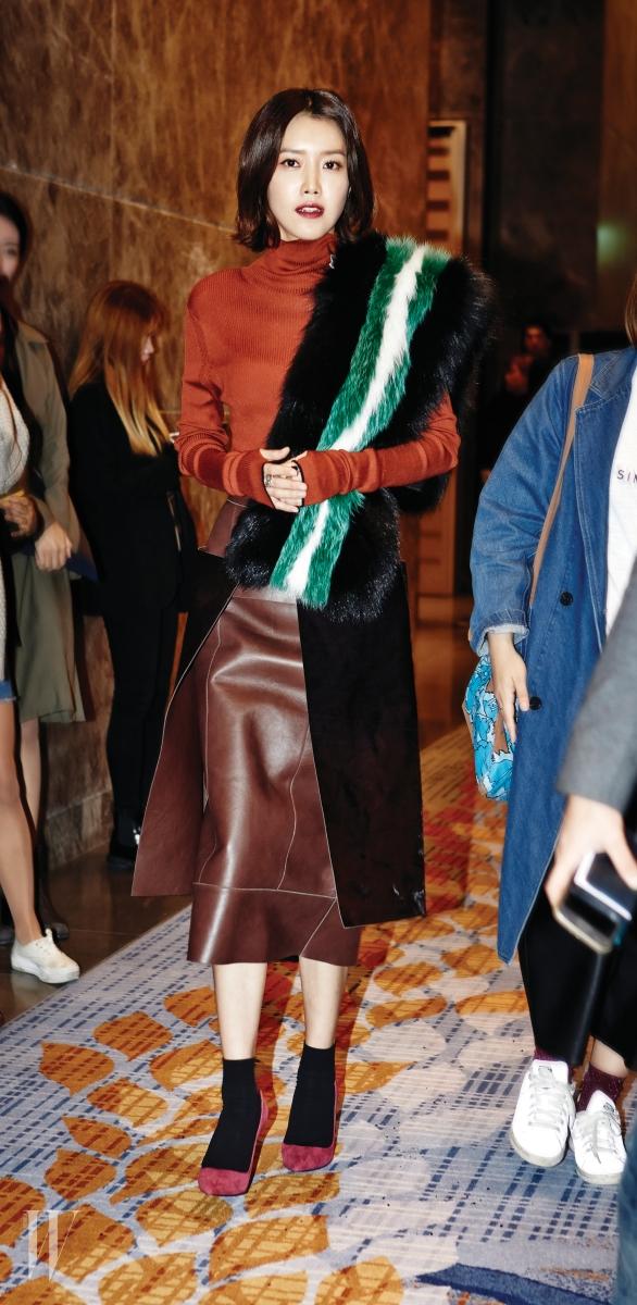 퍼 머플러, 오렌지색 터틀넥, 송치 가죽 스커트는 모두 Fendi 제품.