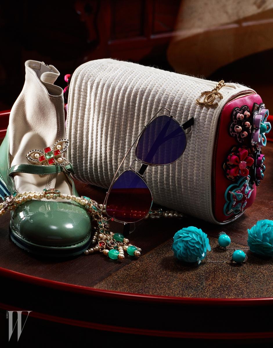 왼쪽부터 | 한국의 버선과 매치된 옥색 슈즈를 보는 듯한 트롱프뢰유 효과로 위트를 더한 가죽 부츠와 나비 브로치, 진주와 유색 스톤 장식 목걸이는 모두 Chanel, 조형적인 프레임의 미러 선글라스는 Dior, 입체적인 꽃봉오리를 연출한 푸른색의 드롭형 귀고리는 Prada, 한국의 전통 베개를 모티프로 한 독창적인 클러치는 Chanel 제품.