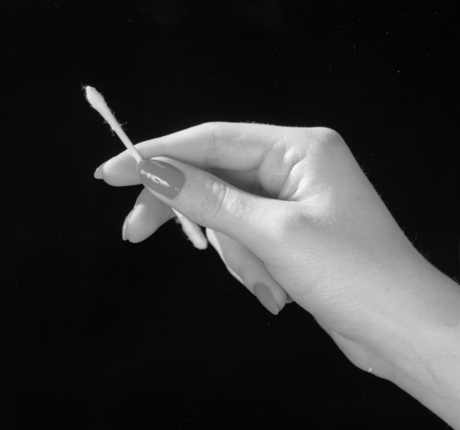 2nd May 1961:  A manicured female hand holding a cotton bud, designed for cleaning the ear.  (Photo by Chaloner Woods/Getty Images)