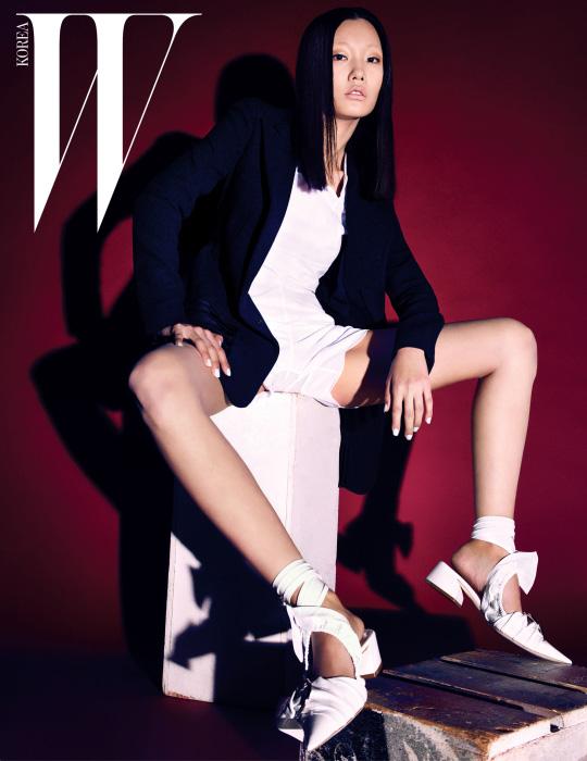 세련된 네이비 장식의 재킷과 흰색 톱, 쇼츠, 페이턴트 소재의 리본 장식 스트랩 슈즈는 모두 Dior 제품.