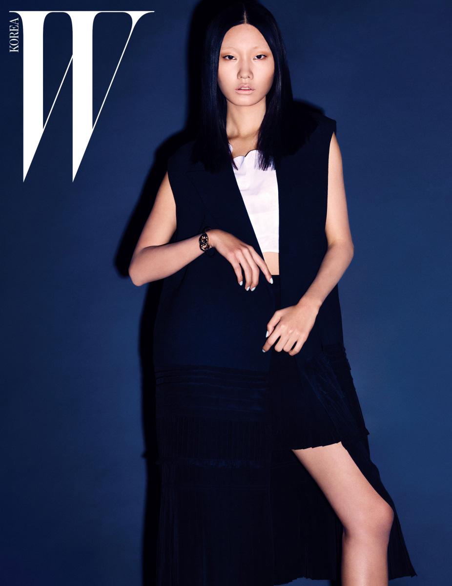 밑단의 프릴 장식이 드라마틱한 느낌을 주는 소매가 없는 네이비 색상 코트와 꽃잎을 연상시키는 네크라인의 크롭트 톱, 짧은 주름 스커트, 골드 뱅글은 모두 Dior 제품.