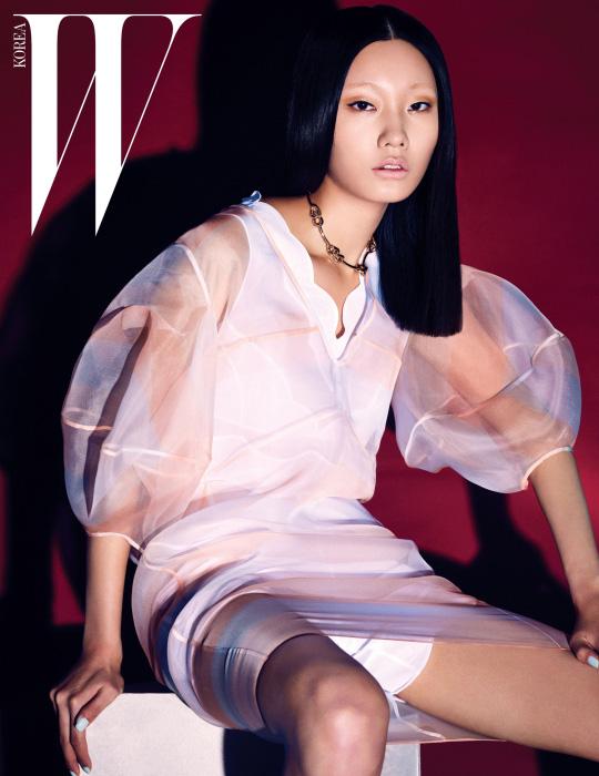 꽃봉오리처럼 볼륨감 있는 소매가 특징인 피치빛 시스루 드레스와 안에 입은 하얀 원피스, 체인 장식 목걸이는 모두Dior 제품.