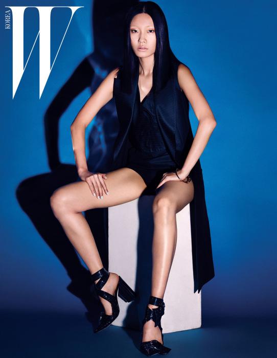 은은한 줄무늬 패턴의 롱 베스트와 톱, 쇼츠, 페이턴트 소재의 리본 장식 스트랩 힐, 골드 뱅글은 모두 Dior 제품.