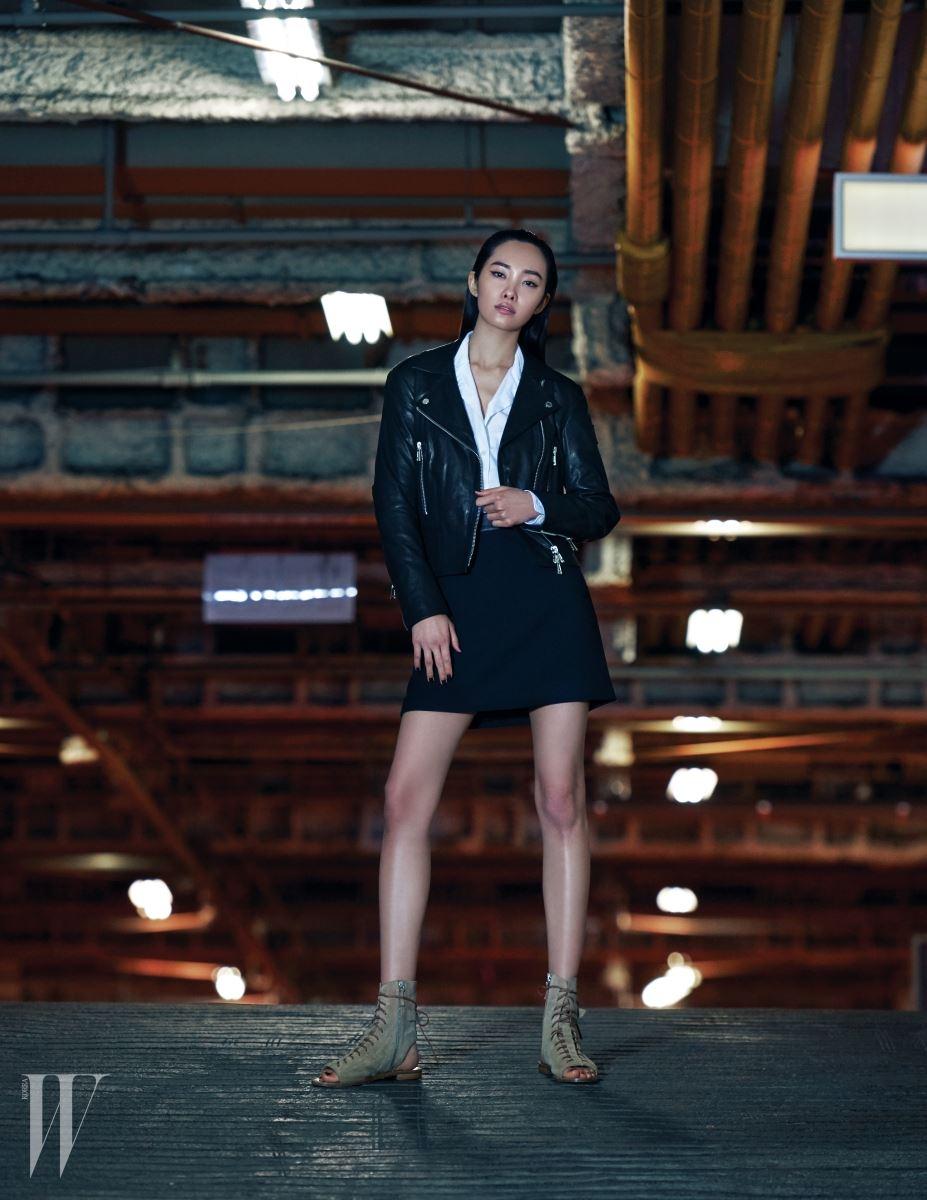 중성적인 디자인의 가죽 바이커 재킷, 흰색 셔츠, 다양한 룩과 잘 어울리는 A라인 미니스커트, 스웨이드 소재 레이스업 슈즈는 모두 Belstaff 제품.