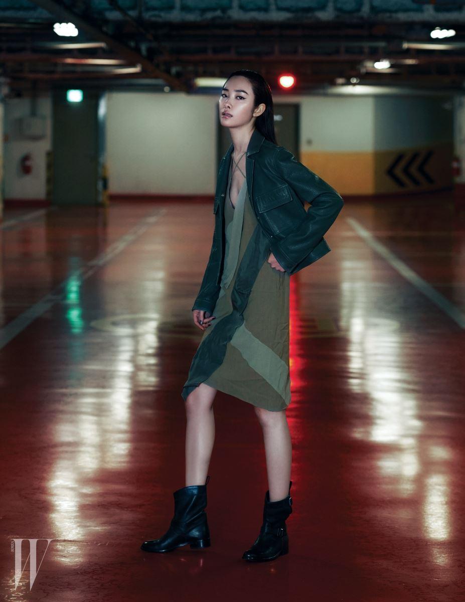 채도 낮은 짙은 초록빛이 멋진 가죽 재킷, 몸을 따라 부드럽게 흐르는 슬리브리스 드레스, 헐렁하게 신을 때 더 멋진 부츠는 모두 Belstaff 제품.
