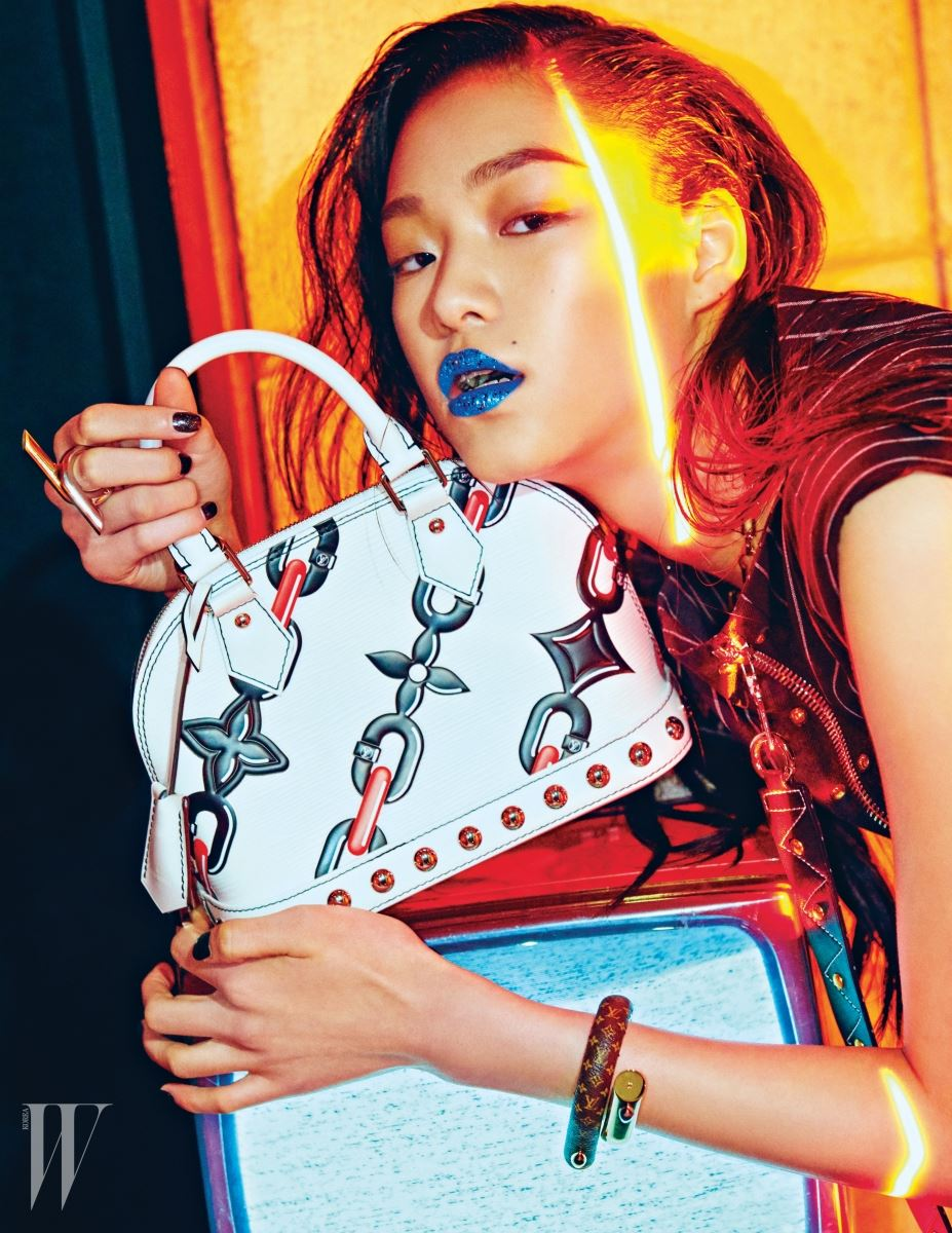 체인 프린트가 담긴 알마 백, 모노그램이 담긴 트위스트 메탈 뱅글과 트위스트 링, 핀 스트라이프 패턴 원피스, 'SEURER' 컬렉션의 메탈 네크리스는 모두 Louis Vuitton 제품.