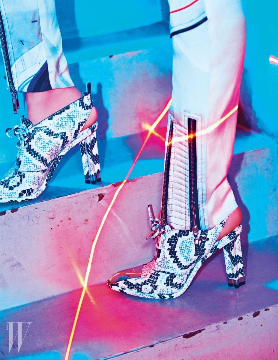 뱀피 패턴의 미래적인 슈즈, 지퍼 장식이 돋보이는 새틴 팬츠는 Louis Vuitton 제품.