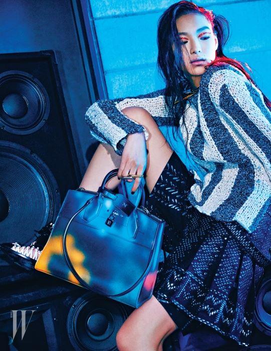 스프레이 프린트의 시티 스티머 백, 줄무늬 니트 톱, 메탈 장식의 팬츠 스커트, 트위스트 메탈 링, 가죽 꼬임 장식 슈즈는 모두 Louis Vuitton 제품.