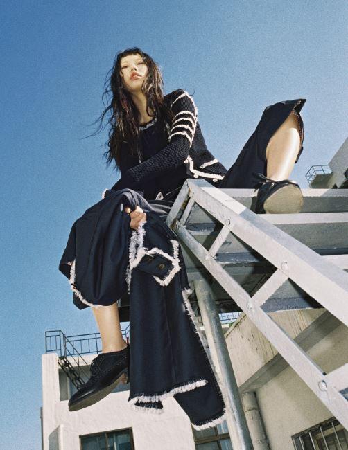 팔 부분의 시그너처 줄무늬가 로컷으로 장식된 카디건과 동일한 색상의 니트 톱, 큼직한 실루엣의 크롭트 팬츠, 손에 들고 있는 로컷 장식 코트, 검은색 윙팁 슈즈는 모두 Thom Browne 제품.