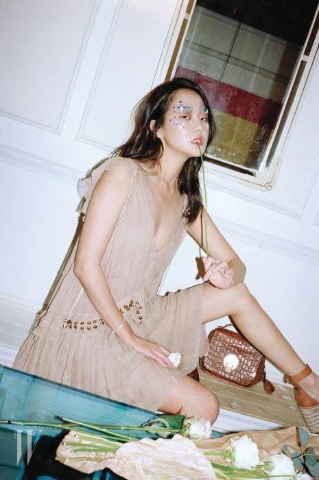 스터드 장식의 시폰 드레스, 토트 겸 숄더 스트랩이 실용적인 스웨이드 카프 스킨 소재의 갈색 인디(Indy) 백, 에스파드리유 굽의 플랫폼 슈즈는 모두 Chloe 제품.