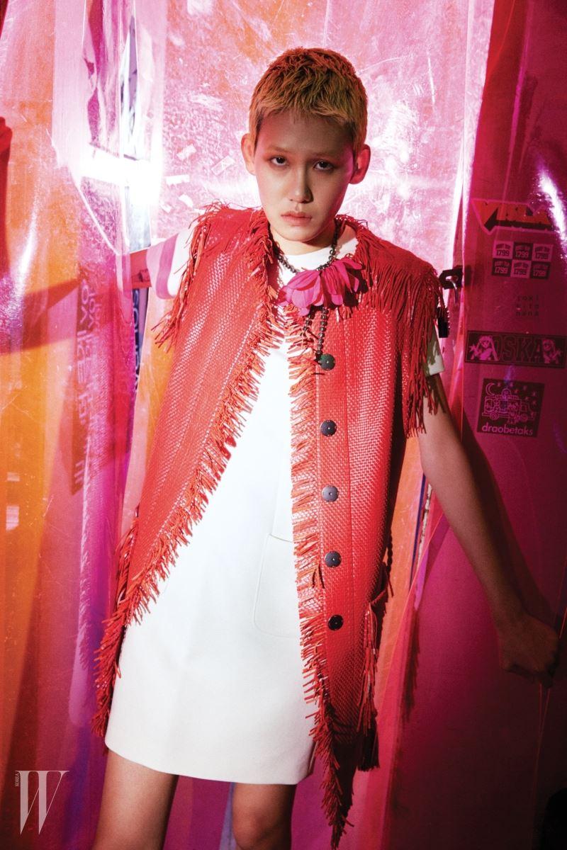 위빙 가죽 소재의 프린지 장식 베스트와 흰색 미니 드레스, 꽃잎 장식 목걸이는 모두 Lanvin 제품.