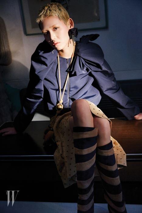 보 스타일이 특징인 네이비 점퍼와 동그란 스터드가 빼곡히 박힌 빈티지한 염소가죽 소재 스웨이드 스커트, 컬러 배색이 특징인 스웨이드 부츠, 태슬 장식 목걸이, 꽃잎 장식 귀고리는 모두 Lanvin 제품.