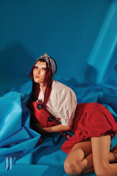 퍼프 소매가 사랑스러운 셔츠 블라우스, 풍성한 푸프 미니스커트, 데님 효과를 준 실크 헤어피스, 꽃 장식이 키치한 미니 백, 진주 장식 드롭 이어링은 모두 Fendi 제품.