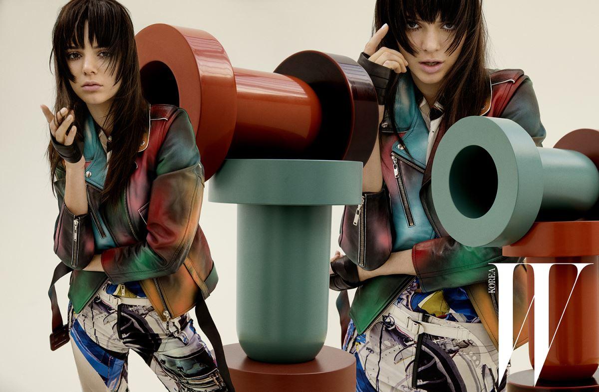 스프레이 효과의 그러데이션 기법이 돋보이는 가죽 바이커 재킷, 그래픽 프린트의 실크 톱과 팬츠, 가죽 벨트, 손을 감싼 검정 가죽 스트랩은 모두 Louis Vuitton 제품.