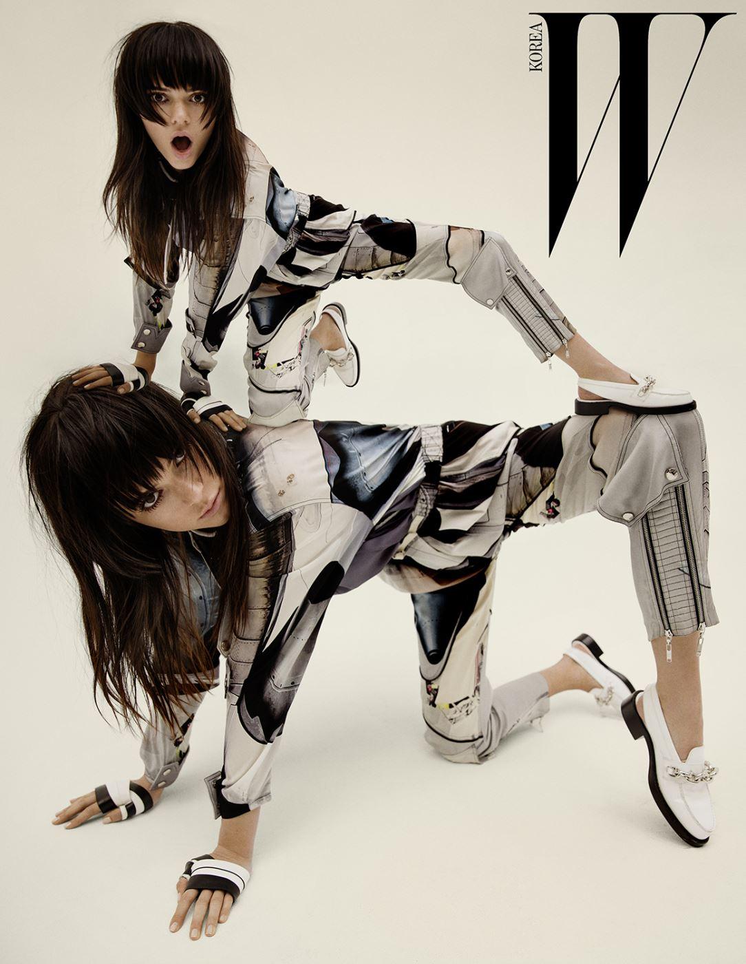 프린트가 돋보이는 실크 톱과 팬츠, 손을 감싼 줄무늬 가죽 스트랩, 메탈 장식 슬링백 로퍼는 모두 Louis Vuitton 제품.