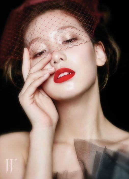 Dior 캡춰 토탈 세럼 파운데이션(020호)으로 맑은 빛이 도는 피부를 연출한 뒤 Benefit 훌라를 이용해 얼굴 라인을 따라 가볍게 음영을 넣어줬다. 입술에는 Bourjois 루즈에디션 벨벳(03호)을 바른 뒤 투명 파우더로 유분기를 잡아줬다. 언밸런스 커팅이 돋보이는 드레스는 Vivatamtam, 보르도 컬러 메시 장식 햇은 Coco de Mer 제품.