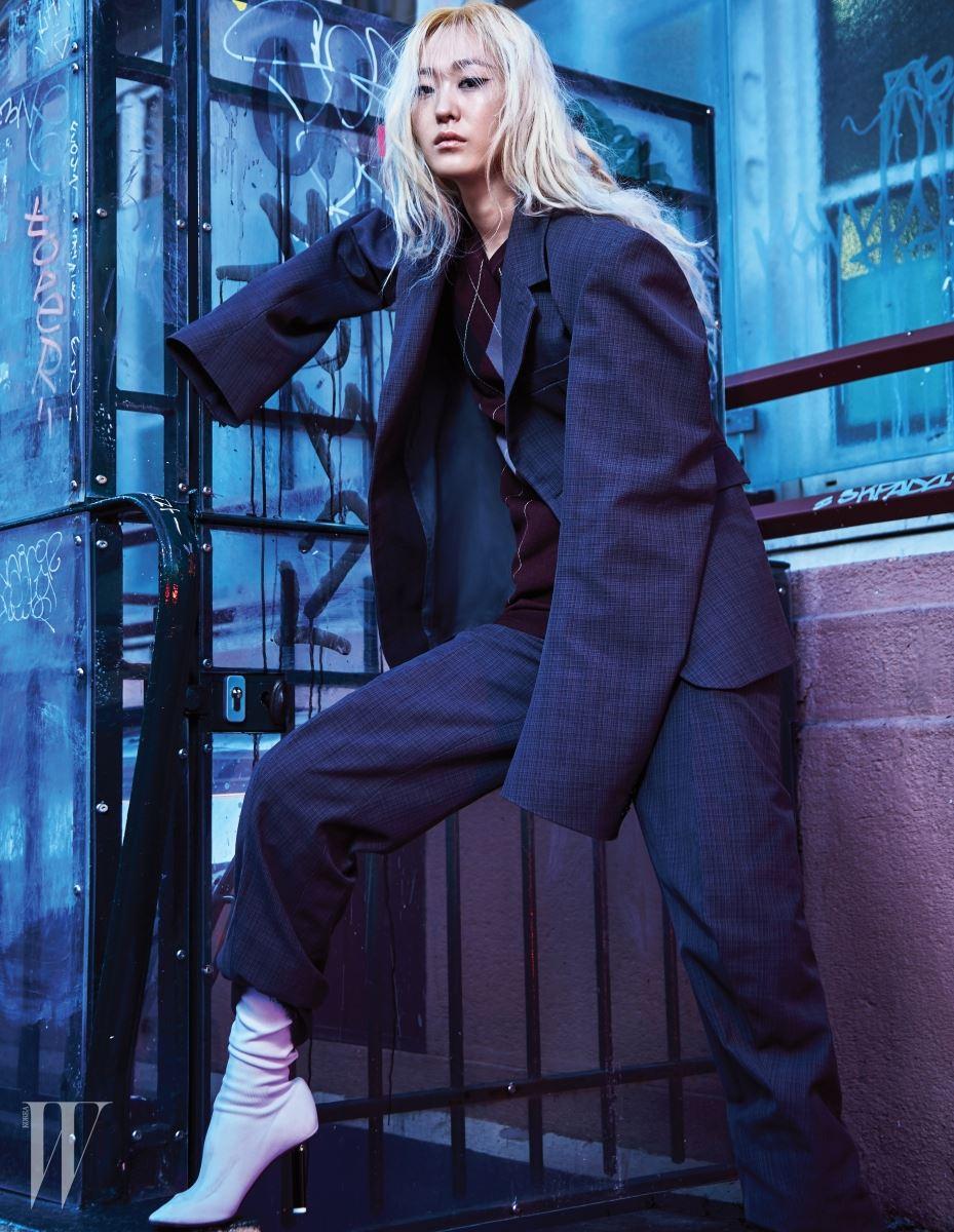 소매가 넓은 재킷과 팬츠, 아가일 패턴 니트 베스트와 양말 형태의 독특한 부츠는 모두 베트멍 제품.
