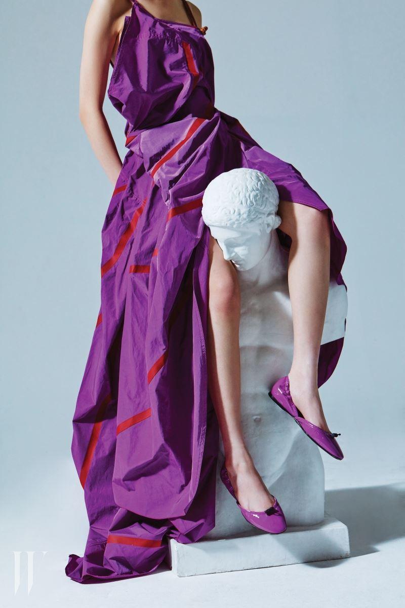 낙하산을 연상시키는 감각적인 주름 드레스, 스포티한 무드의 스트링이 달린 포라색 페이턴트 플랫 슈즈는 보테가 베네타 제품. 가격 미정.