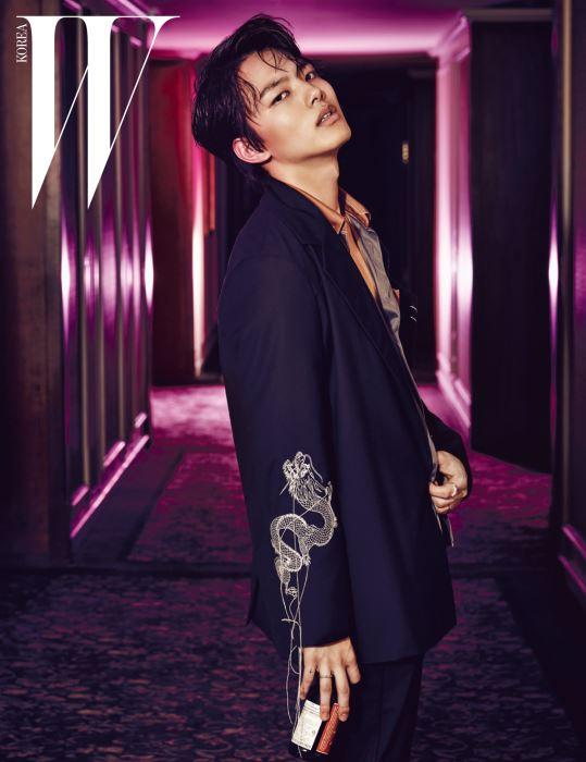 스트라이프 실크 셔츠는 Prada, 소매에 용무늬를 수놓은 재킷은 R. Shemiste, 검은색 팬츠는 Juun. J 제품.