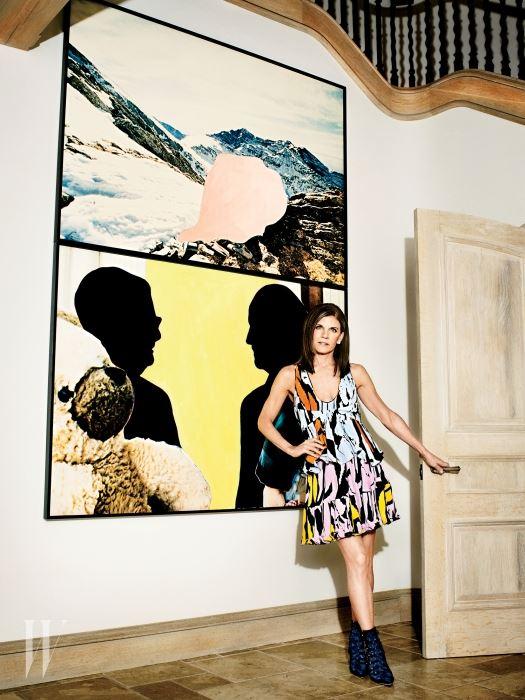 휘트니 미술관의 임원인 낸시 크라운 뒤로 존 발데사리의 '물체를 든 두 형상 위의 분홍 형체들(산악 풍경 속에) (2003)' 이 걸려 있다. 톱과 스커트, 부츠는 모두 디올 제품.