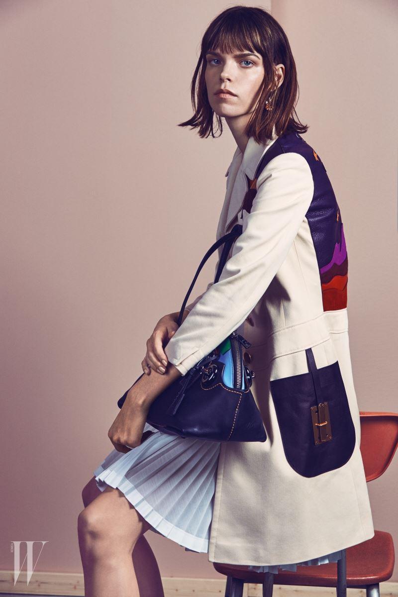 반달 모양의 패치워크 장식 백, 뒷부분에 동화적인 패턴이 장식된 코트, 주름 장식 원피스, 장미 모양 드롭 이어링은 모두 Coach 제품.