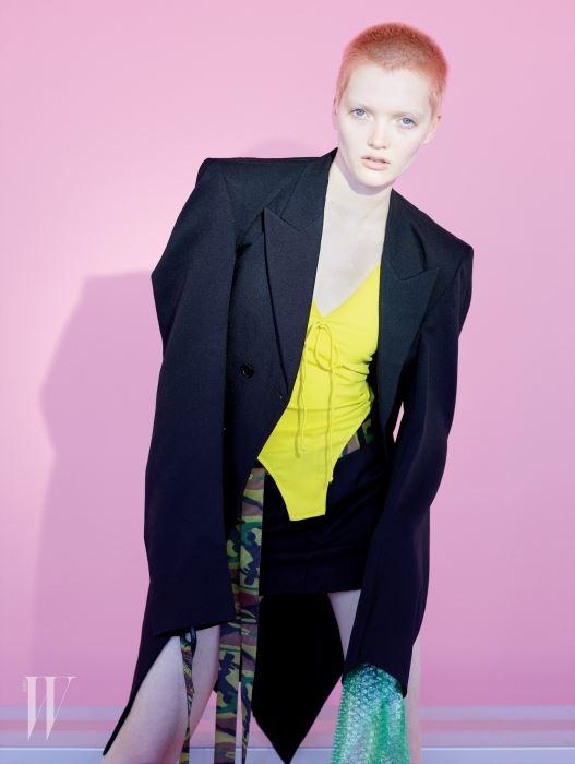 노란색 보디슈트와 검은색 스커트, 재킷은 모두 Vetements 제품. 카무플라주 벨트는 스타일리스트 소장품. Beauty note: Joico의 피어리 코럴 제품으로 머리카락을 밝게 물들였다.